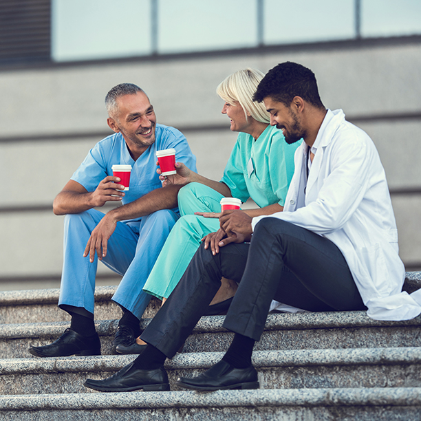 Team of happy medical workers relaxing on stairs during their coffee break and communicating.